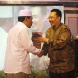 Cinderamata: Dr. Muhammad Syafi'i Antonio, M.Ec. memberikan cindera mata berupa buku karyanya kepada KH. Moh. Hasan Mutawakkil Alallah, SH., M.M.