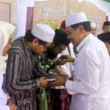 KH. Moh. Hasan Mutawakkil Alallah melaunching buku dan membagikan kepada para kiai dan habaib yang hadir diacara lailatul qiroah